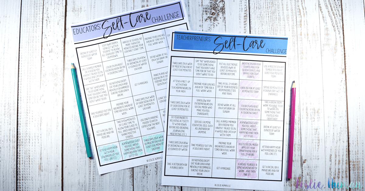 A wide, horizontal photograph of two sheets of paper on a whitewashed wood grain backdrop. The papers say Educators' Self-Care Challenge and Teacherpreneurs' Self-Care Challenge and have challenge boards of self-care activities. Both papers have a row or a column colored in to show completion with colored pencils sitting next to them.