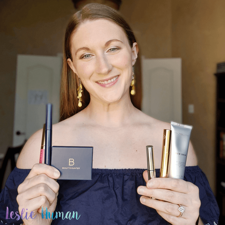 This is a photograph of Leslie Auman Hirgelt, a Beautycounter Consultant, holding six safer beauty products in her hands.